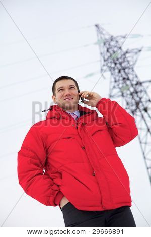 Young businessman in red jacket is calling phone near power line.