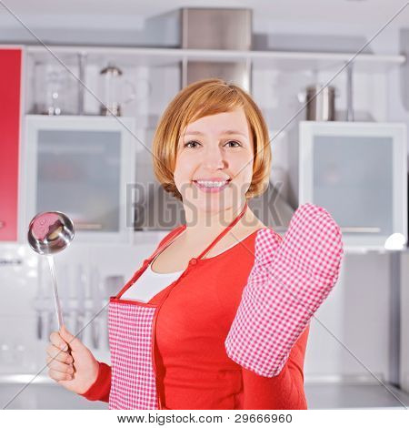 Smiling girl in red silver kitchen wearing apron holding ladle and tack.