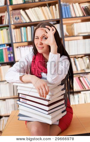 Beautiful girl sitting on table in library with books and showing ok sign.