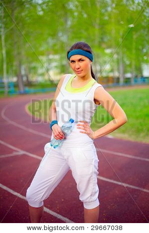 Pretty sport girl standing on running track in forest holding water bottle outdoor