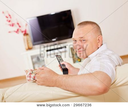 Middle aged man sitting on sofa holding remote control and cup watching television indoor