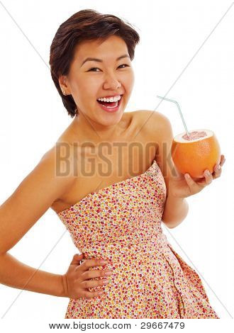 Beautiful asian girl in sundress standing and cheerful laughing with improvised cup of grapefruit juice. Isolated on white background, mask included