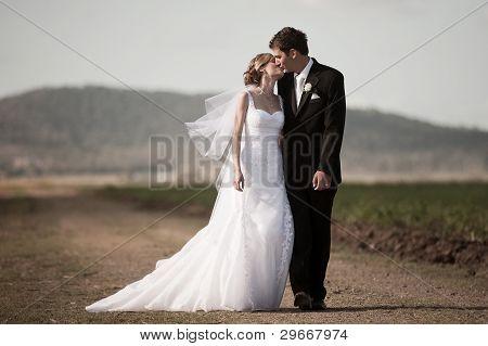 Bride And Groom Walking Down A Rural Road