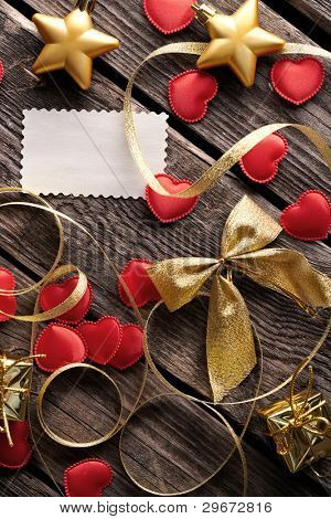 Small hearts with gold curved ribbon, gold bow and blank gift tag on old wood.