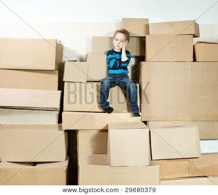 Kind sitzt auf der Oberseite des Stapels verpackt Boxen.