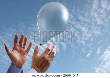 Releasing a balloon into the air concept for dreams and aspirations with copy space on the balloon and sky