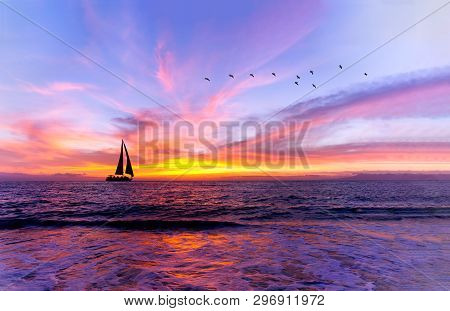 poster of Ocean Sunset Sailboat Is A Vibrant Ocean Sunset With A Sailboat Sailing Along The Water With A Flock