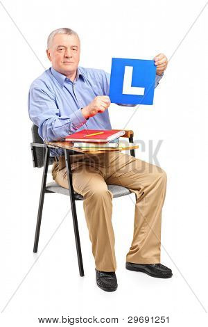 A senior man sitting on a school chair holding a L plate isolated on white background