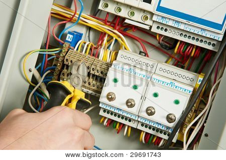 One electrician working on a industrial panel mounting and assembling new wiring with plyers