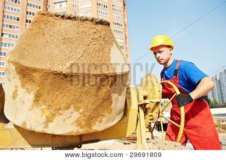 builder laborer man working with front of concrete cement mixer at construction site