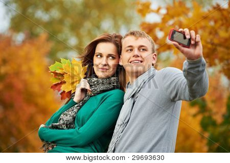 Two Smiling young people taking a picture with mobile phone in autumn park outdoors