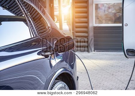 poster of Charging An Electric Car At A Car Repair Shop Service Garage. Refueling For Electric Cars E-mobility