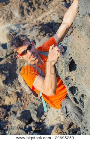 Young man in glasses with backpack climbing