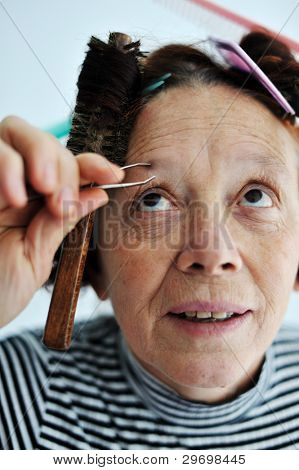 Senior female tweezing eyebrow