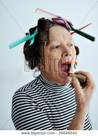 Senior woman putting lipstick