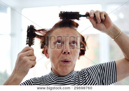 Senior lady hairdressing with many combs