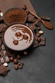 Glass Bowl Of Chocolate Cream Or Melted Chocolate, Pieces Of Chocolate And Hazelnuts On Dark Concret poster