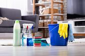 Close-up Of Cleaning Products And Tools On Hardwood Floor In Living Room poster