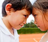 Siblings rivalry - two kids at the tennis court looking competitive