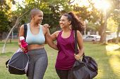 Cheerful smiling friends in sportswear holding gym bag and bottle in park. Multiethnic women going t poster