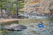 paddler in an inflatable packraft on a mountain river in early spring - Poudre River above Fort Coll poster