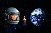 a small child imagines himself to be an astronaut in an astronauts helmet. Elements of this image f poster