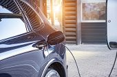 Charging An Electric Car At A Car Repair Shop Service Garage. Refueling For Electric Cars E-mobility poster