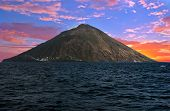 Sunset over Stromboli volcano seen from the boat. Stromboli is one of the eight Aeolian islands and  poster