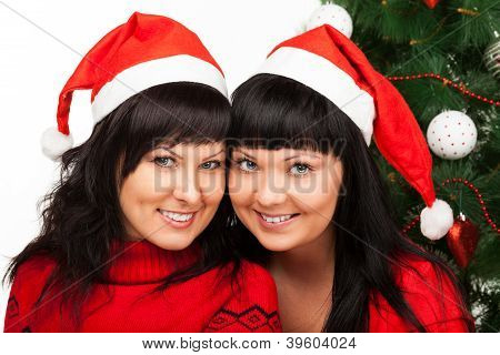 Two girls in red caps smile near Christmas tree