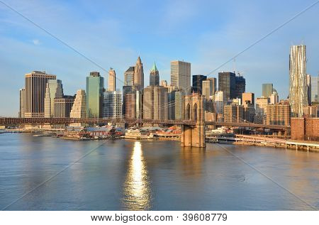 New York City skyline with Brooklyn Bridge and Lower Manhattan view in early morning sun light