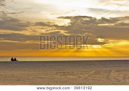 Couple  Sitting On The Beach Watching Sunset