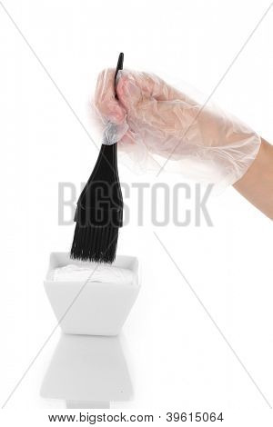 woman's hand in a glove dips the brush in hair dye, on white background