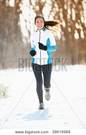Winter running. Woman runner trail running cold winter forest landscape. Mixed race Asian / Caucasian female cross country running in warm clothes