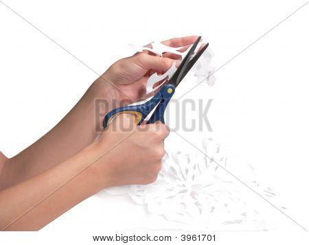 La mano femenina se recorta un copo de nieve de un Paper Scissors
