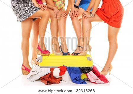 A picture of five women with their sexy legs put on a suitcase over white background