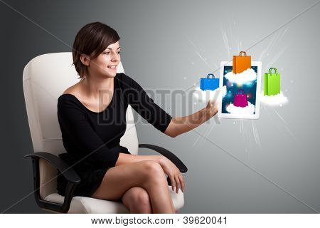 beautiful woman holding modern tablet with colorful shopping bags on clouds