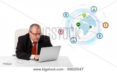 businessman sitting at desk and looking laptop with globe and social icons, isolated on white