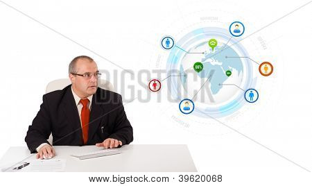 businessman sitting at desk and typing on keyboard with globe and social icons, isolated on white