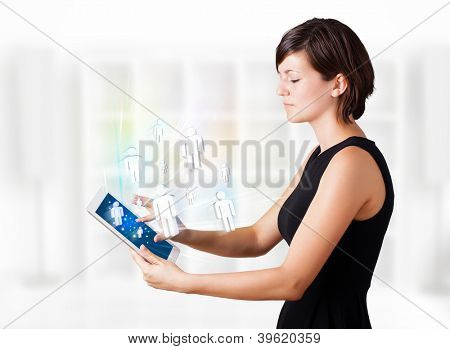 Young business woman looking at modern tablet with social icons