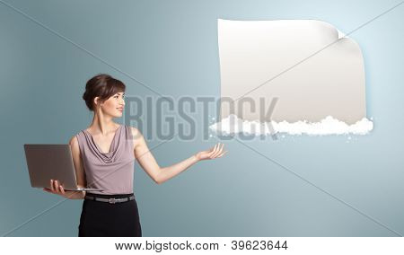 Attractive young woman holding a laptop and presenting modern copy space on clouds