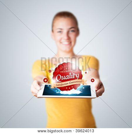 Young woman holding tablet with red quality label in clouds
