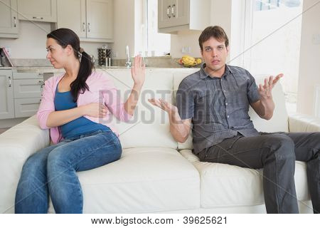 Two people sitting on the couch in the living room while waving each other away