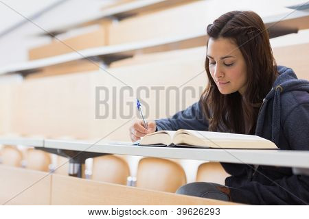 Girl reading a book and writing notes at the lecture hall