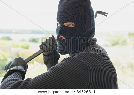Robber with a crow bar in a home