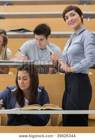 Students working while teacher smiling at the lecture hall