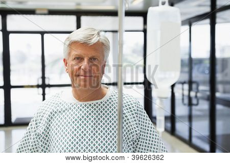 Patient standing in the corridor of the hospital with IV drip