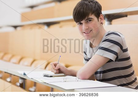 Student sitting at the lecture hall while holding a pen and smiling