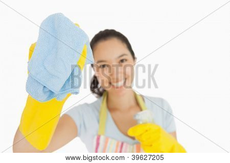Laughing woman wiping with a blue rag wearing rubber gloves and apron