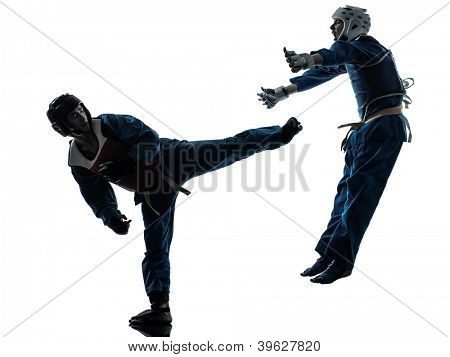 one causasian manman woman couple exercising karate vietvodao martial arts in silhouette studio isolated on white background