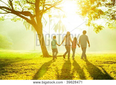 Happy Asian family holding hands walking over green lawn